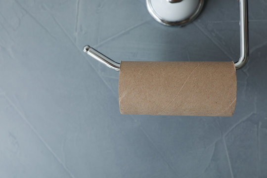 Holder with empty toilet paper roll on gray wall