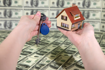 The man is holding a smaller copy of the house and the keys. Buying a property. Background from dollar bills. Money for rent.