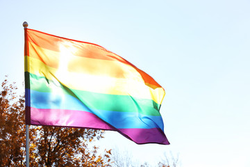 Rainbow LGBT flag and space for text on blue sky background. Gay rights movement