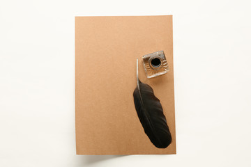 Feather pen, inkwell and sheet of paper on white background, top view. Space for text
