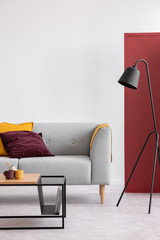 Black lamp next to grey sofa with pillows in grey and red living room interior with table. Real photo