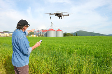 Farmer using drone in a wheat field with silos in Chianti region, Tuscany, Italy