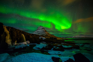 Kirkjufell is amazing place in the north-west of Iceland. It is exciting to wait for a few monents of green lights. In the foreground is waterfall. The northern lights are reflecting in the lake...