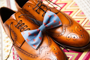 Still life with brown men's shoes and blue bow tie with printed skulls