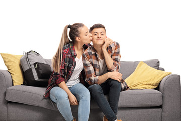 Teenage girl kissing a boy on a sofa