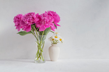 Pink peonies in a vase on a light background