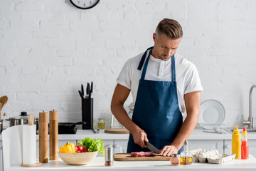 Mature man cutting meat for dinner in kitchen Wall mural