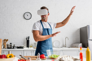 man in virtual reality headset gesturing at kitchen