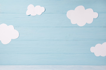 Cute children or baby card, white clouds on the blue wooden background