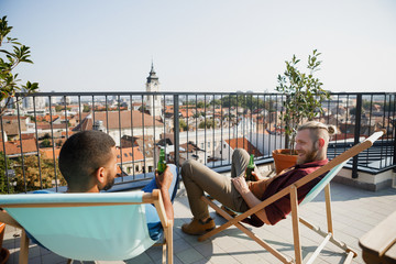 Two smiling men friends chatting on a terrace and enjoying drinking beer.