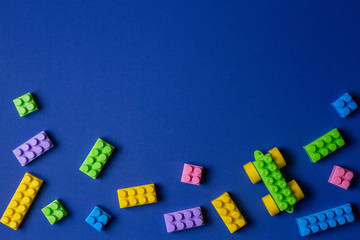 Colorful plastic toy car building blocks on blue background