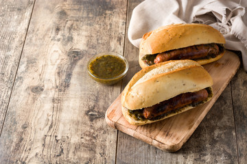 Choripan. Traditional Argentina sandwich with chorizo and chimichurri sauce on wooden table. Copyspace