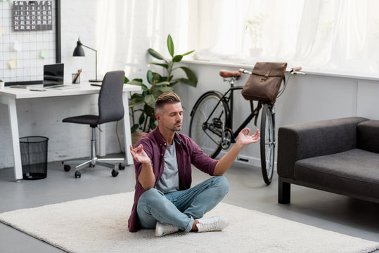 concentrated man sitting on floor practicing yoga at home office