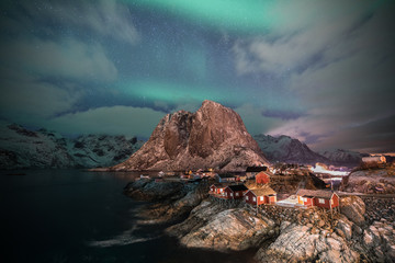 Fisherman village with Aurora in the background travel concept world explore northern light / Lofoten Norway