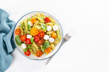 healthy fusilli pasta with pesto sauce, roasted tomatoes, mozzarella