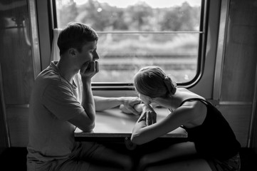 Couple of lovers traveling in train. Mood black white portrait of romantic pair siiting in wagon near window with self reflections in it. Boy and girl looking at each other and telling secret. Trip.