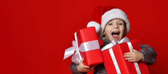 Funny smiling child in Santa red hat holding Christmas gift in hand.