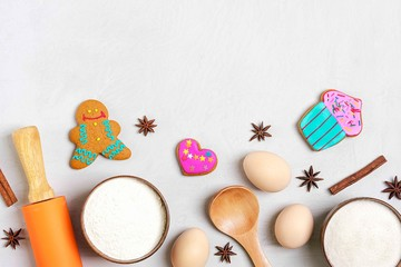 Ingredients for making gingerbread - flour, sugar, eggs, cinnamon, cloves, nuts, bakeware, rolling pin on a gray concrete background Flat lay