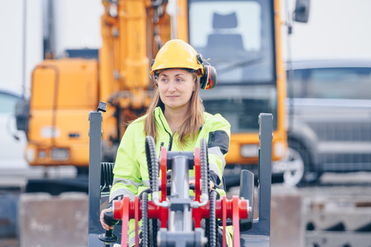 Female in reflective safety clothing operating front end loader at work site