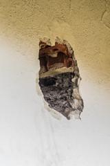 dziura w ścianie budynku