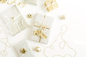 Christmas, New Year holiday composition with golden gift boxes, decorations on white background. Flat lay, top view of gifts packaging.