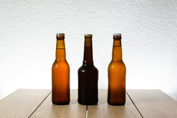 Cold beer bottle without label on wooden table back-lit isolated on white background
