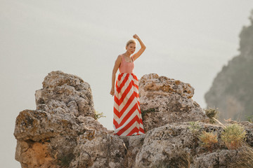 An attractive blonde woman in the red and white dress dancing with one hand over her head on the top of the cliff with the mountain in the background. Mountain view. Evening in Spain