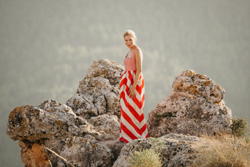 A cute blonde lady in the red and white dress dancing on the top of the cliff with the mountain in the background. Mountain view. Evening in Spain