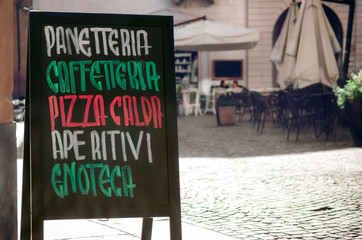 italian coffe bar signboard with the words panetteria (bakery), caffetteria(cafeteria), pizza calda (hot pizza), aperitivi (aperitif) and enoteca (wine shop)