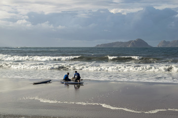 two surfers sitting on the shore of the beach in front of the waves