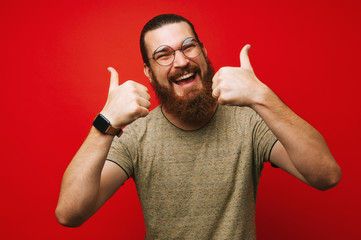 Happy smiling bearded man showing thumbs up over red background