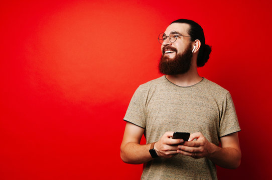 Happy man with beard using phone over red background with copyspace