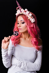 The Unicorn Girl. Young beautiful girl in the image of unicorn with pink hair and stylish make-up, copy space.