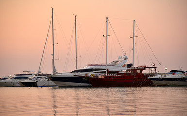 Pink sunset on the sea lights yachts
