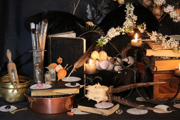 Black candle Magic Ritual. Antique Magic Book. Witchcraft  Peacock feathers and candle background.