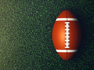 American football ball on grass lit by spotlight seen from the top, Game night background