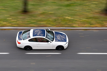 Very quickly driving white ecological solar car on a city street