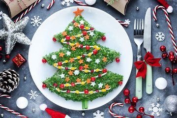 Christmas new year meal idea - creative appetizer salad like a christmas tree with festive decoration from greens and vegetables