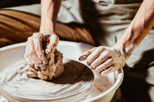 Artisan potter prepares material clay for pottery. Man knead clay before molding. Male sculptor is pugging and kneading clay for creating ceramics in his studio