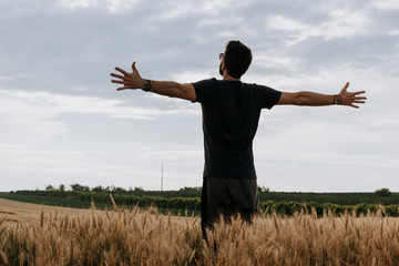 Young man in the wheat field with spread arms