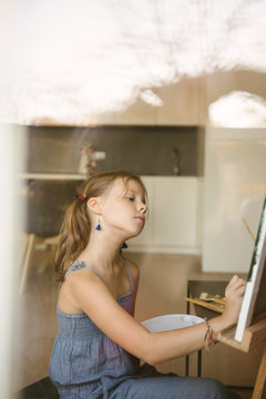 Little girl drawing on canvas at home