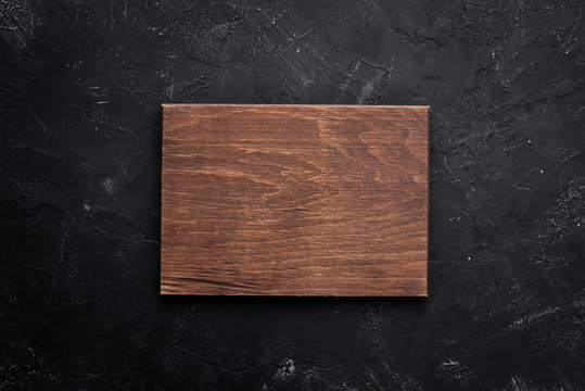 Kitchen board on black stone background. Top view. Free space for your text.