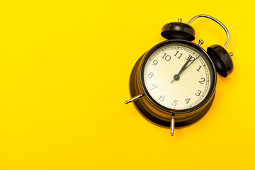 Black alarm clock with yellow background.