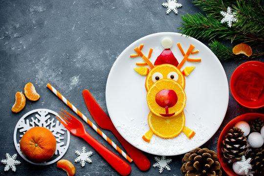 Fresh orange slices santa reindeer, Christmas food art, funny fruit snack idea for kids