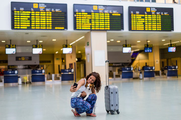 traveler woman and her dog taking a picture with mobile phone at the airport. information screens background. travel and transportation with technology concept.