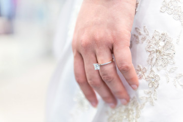Closeup of princess cut diamond engagement ring on woman's female hand, white wedding dress, background
