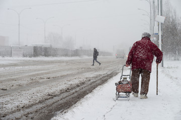 A snowstorm in the city. An elderly woman with a cane and a bag on wheels goes along the road during a snowstorm. Selective focus.