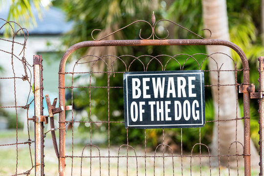 Beware of the dog sign on closed rusty fence gate with rust at residential neighborhood with house, home in background and nobody