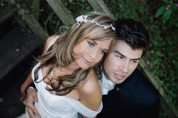 Bride and groom standing on wooden steps