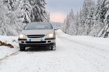 A car on a dangerous and slippery snowy mountain road